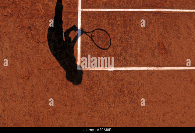 The shadow of a tennis player preparing to receive during a game on a clay court - Stock Image