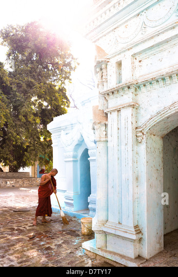 Buddhist monk cleaning paving outside a small temple near the famous U Bein teak bridge, Amarapura, near Mandalay, - Stock Image