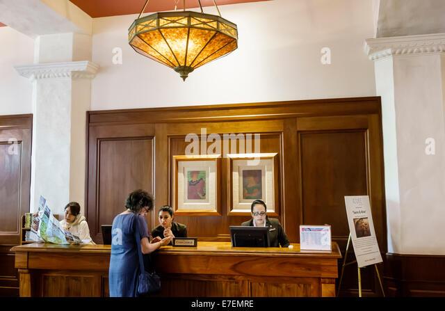 Waikiki Beach Honolulu Hawaii Hawaiian Oahu Royal Hawaiian hotel lobby concierge desk woman coworkers employee job - Stock Image