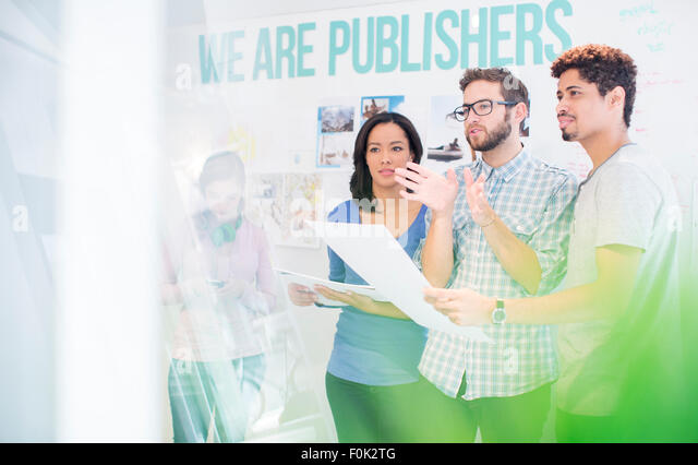 Publishers reviewing and discussing proofs in office - Stock Image