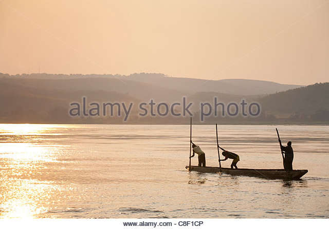Young Congolese fisherman paddle their pirogue across the Congo River. - Stock-Bilder