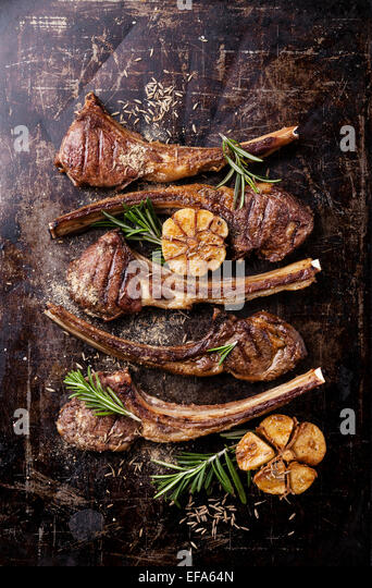 Roasted lamb ribs with spices and garlic on dark steel background - Stock Image