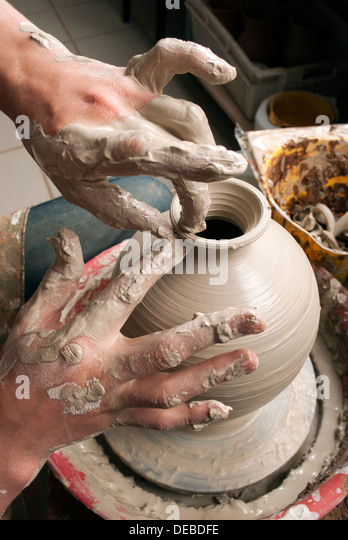 hands of a potter, creating an earthen jar on the circle - Stock Image