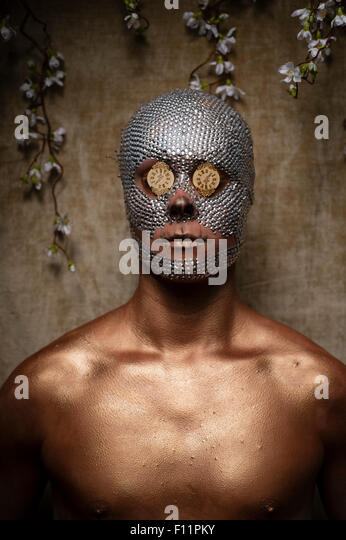 'Day of the Dead' theme portrait - a young man with crystal sequins glued to his face and mini clock faces - Stock Image