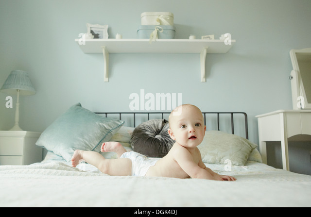 Baby boy lying on front on bed - Stock-Bilder