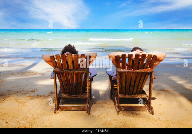 couple resting on the beach - Stock Image