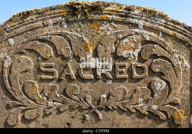 Sacred - on a tomb stone in a Cotswold churchyard - Stock Image