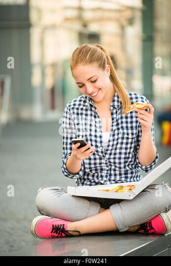 Teenager eating pizza in street and browsing internet on phone - Stock Image