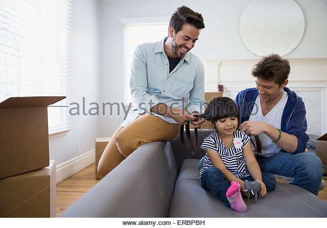Homosexual couple fixing daughter hair sofa moving boxes - Stock Image