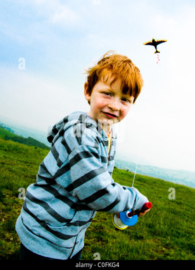 Small boy on a hill top in South Wales UK running in the wind and flying a kite - Stock Image