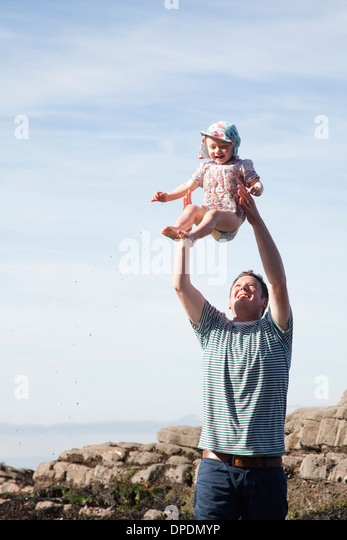 Father throwing child in air on beach - Stock-Bilder