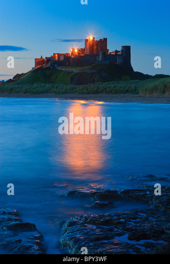 Bamburgh Castle at sunrise on the east coast of Northumberland, England. - Stock Image