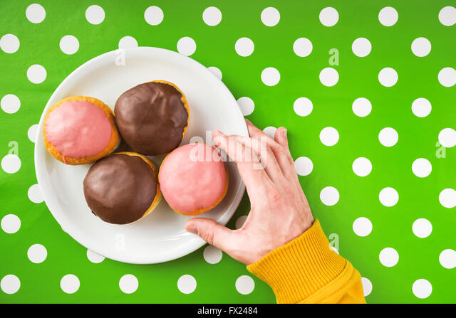 Male hand picking donut with sweet strawberry topping from a plate, top view of homemade tasty donuts on kitchen - Stock Image