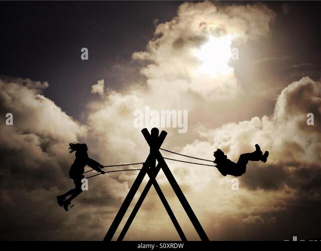 Children play on a swing in a holiday park at Loch Ken, Scotland. - Stock Image
