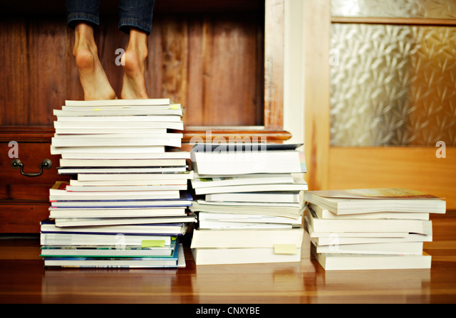 Girl stands tiptoe on pile of books - Stock Image