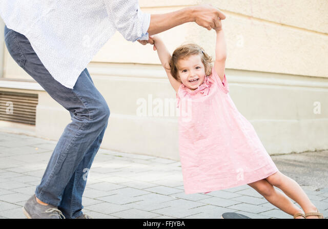 Father and daughter on skateboard - Stock Image