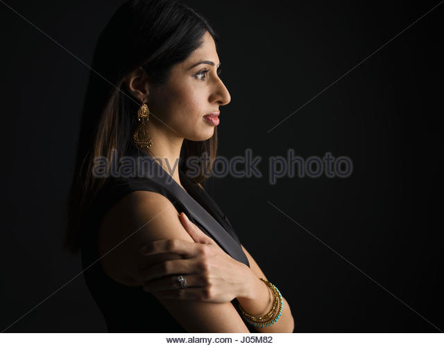 Profile portrait serious Indian woman looking away against black background - Stock Image