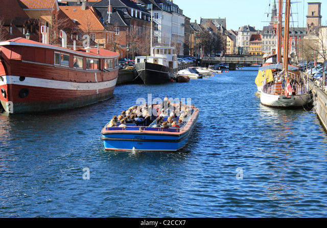 At springtime one of the first top-open tourist boats on canals in Copenhagen - Stock Image
