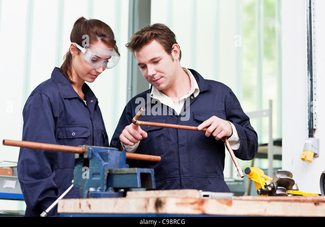 Professional plumber with apprentice class - Stock Image