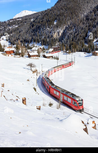 Red train of Rhaetian Railway passes in the snowy landscape of Arosa, district of Plessur, Canton of Graubunden, - Stock-Bilder