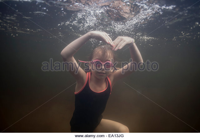 Portrait of girl swimming underwater making heart shape with arms - Stock Image