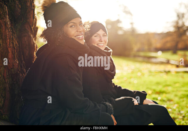 Two young women sitting in autumnal park and smiling at camera.Sunny - Stock Image