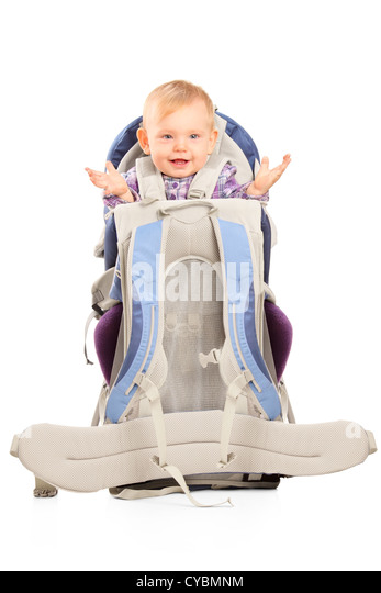 Happy baby girl in a baby carrier for hiking isolated on white background - Stock Image