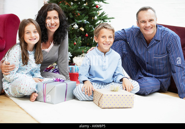 Happy Family in Front of Christmas Tree, portrait - Stock Image