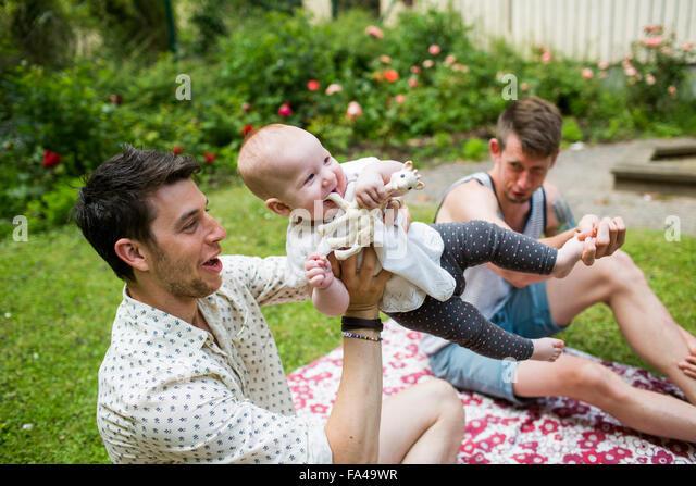 Happy gay men playing with baby girl at yard - Stock-Bilder