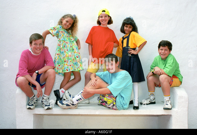 Group of young junior boys and girls 6 to 10 years pose for the camera in a selection of colourful clothing styles - Stock-Bilder