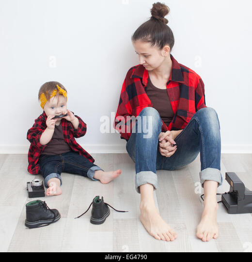 Mother and baby in red checkered shirts and jeans - Stock Image