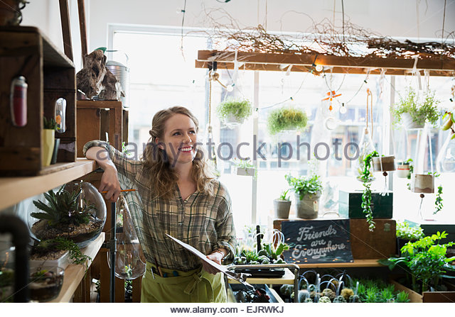 Smiling terrarium shop owner taking inventory with clipboard - Stock Image