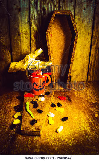 Spooky scene of a ghostly mummy hand picking up a jelly candy container in a spill of halloween fun. Trick of treats - Stock Image