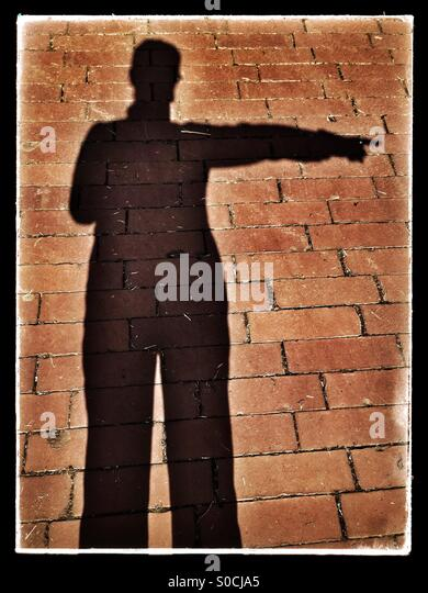 Shadow silhouette selfie of person pointing to the right, over brick pavement, with vintage sandstone texture overlay - Stock Image