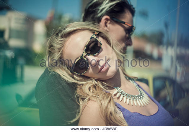 Young woman leaning against young man - Stock-Bilder