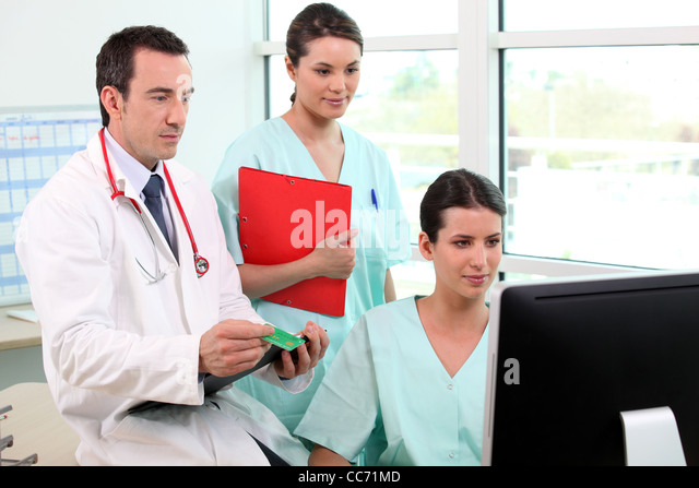 The hospital workers gathered around computer - Stock Image