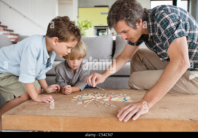 Man playing pick up sticks with his sons - Stock Image