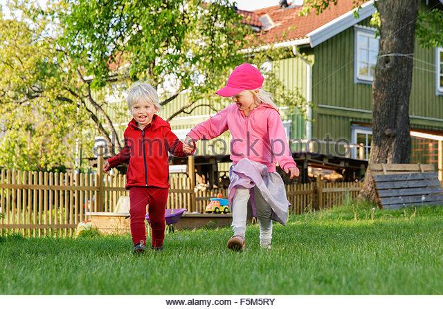 Sweden, Sodermanland, Jarna, Children (2-3, 4-5) playing on front yard - Stock Image