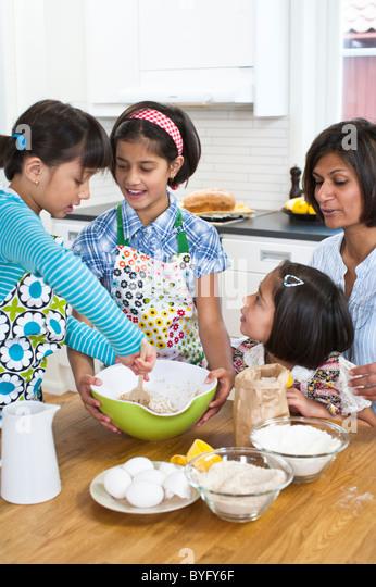 Mother baking with girls in kitchen - Stock-Bilder