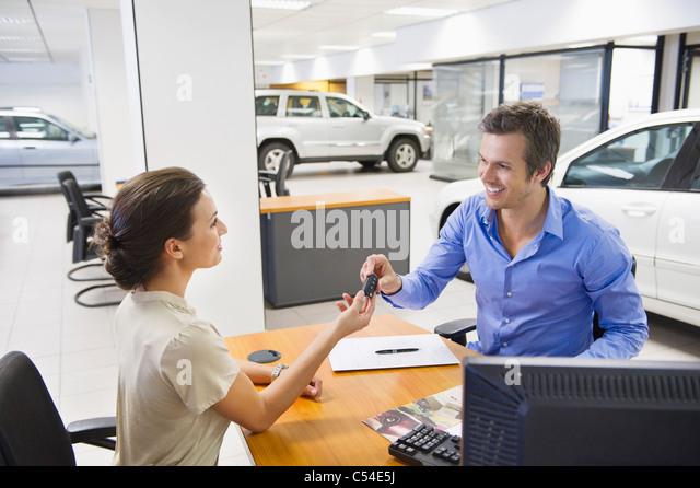Saleswoman handling car key to a man - Stock Image