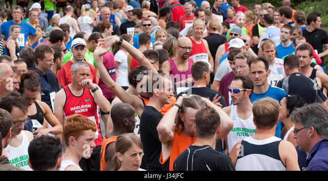 Runners milling about before the start of a 10km road race - Stock Image