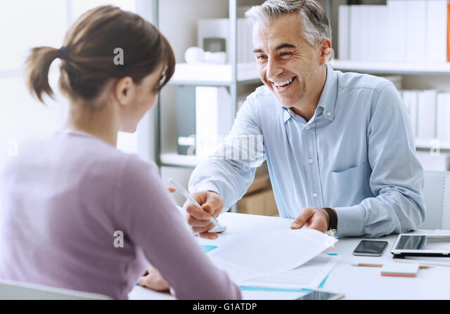 Young woman having a business meeting and signing a contract, recruitment and agreement concept - Stock-Bilder