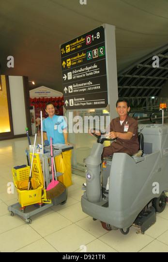 Bangkok Thailand Suvarnabhumi International Airport BKK terminal concourse gate area cleaning staff Asian man woman - Stock Image