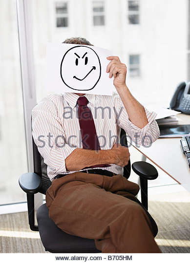 Businessman holding picture of angry face - Stock Image