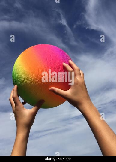 Childs hands catching a rainbow colored rubber ball against a hazy blue sky - Stock-Bilder