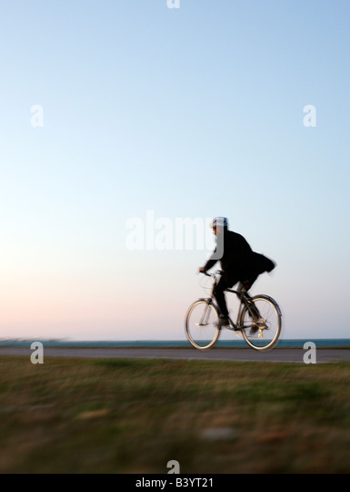 Man in suit riding bike along Chicago lake front at dusk (healthy lifestyle) - Stock Image