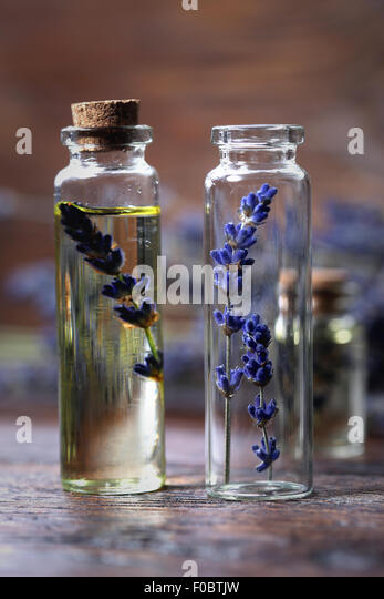 Lavender oil in a glass bottle on a wooden table - Stock Image