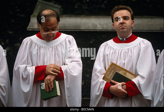 A chorister checks the time after singing hymns outside the Norman-built St Bartholomew the Great church in Smithfield - Stock Image
