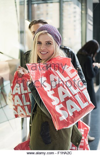 Young couple on street with sale shopping bags,  New York, USA - Stock Image