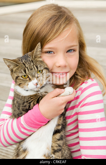 Smiling girl holding cat outdoors - Stock Image